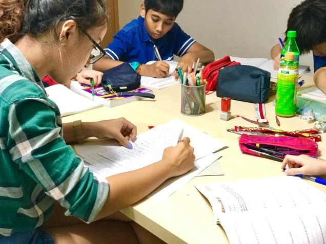 Punggol Primary Mathematics and English Tutor marking their work.